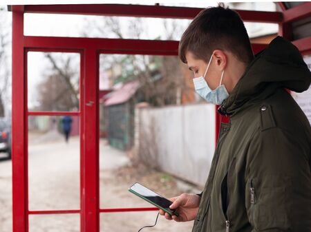 guy in a medical mask stands at a bus stop. isolated to avoid viral disease covid-19 measles flu chickenpox cold.