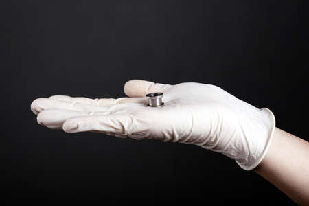 ear jewelry, hand in a white disposable glove holds in his palm a tunnel for the ear of silver color on a dark background close-up.