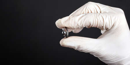 silver piercing ring, accessory for piercing in hand on a dark background.