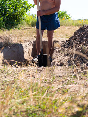 gravedigger digs a grave. a man digs a hole with a shovel in a cemetery.