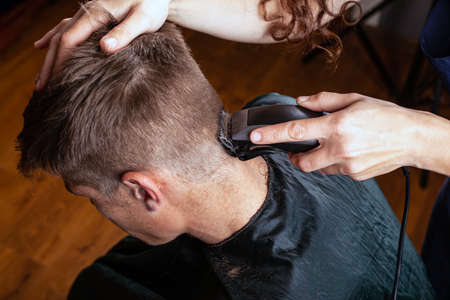 trim the hair with a trimmer on the back of the head, hairdresser, barbershop.