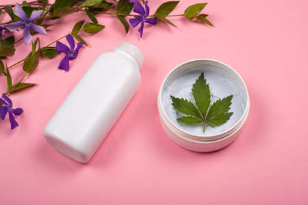 white bottles with body cosmetics with marijuana leaf on a pink background with violet wildflowers. skin care, beauty, cosmetics with cannabis
