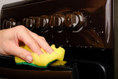 Female hand cleans the gas stove with a sponge with white foam, cleaning the surface. hygiene at home, appliances.