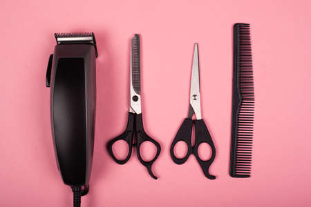 hairdressing tools, hair cutting tools, hair clipper and scissors on pink background top view.