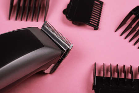 hairdressing tool, hair clipper with nozzles on a pink background closeup.
