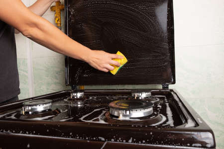 cleaning the kitchen, surface cleaning on the gas stove, washing the stove with a yellow washcloth, household kitchen appliances.