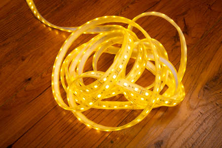 skein of led strip with warm yellow light close-up. 免版税图像