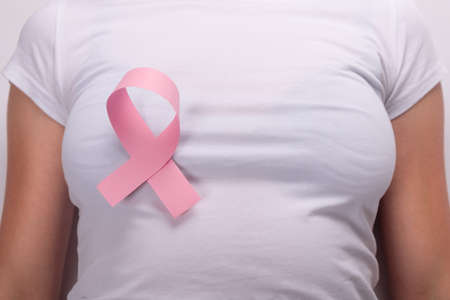 pink ribbon on the female breast, breast cancer fight symbol. 免版税图像