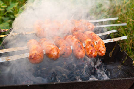 pork sausages in the smoke prepare for grill, B-B-Q food sentenced in the fresh air.