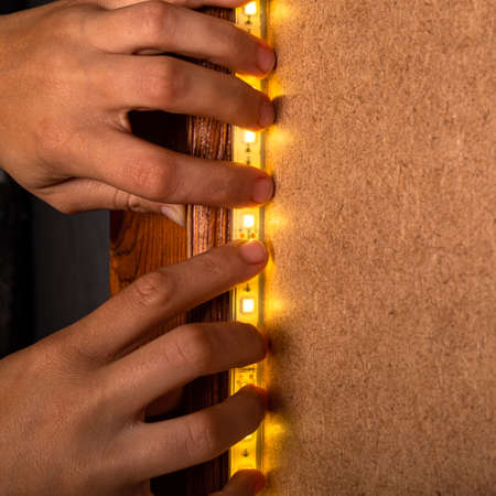 the master installs LED strip warm light for decorative lighting at home, office close-up. 免版税图像
