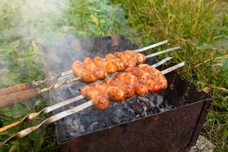 summer picnic, food cooked outdoors, pork sausages on a skewer with a fried crust in smoke close-up on the grill.