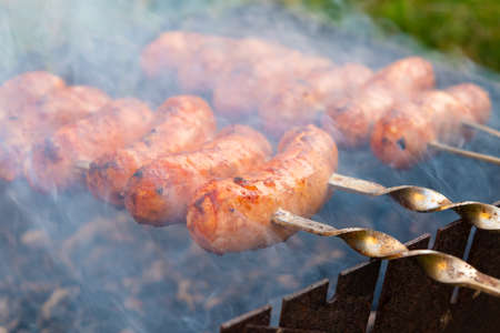 fried sausages on skewers on the grill.
