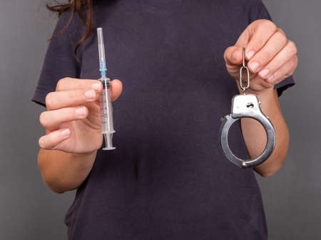 punishment for drug use, handcuffs and syringe close up.