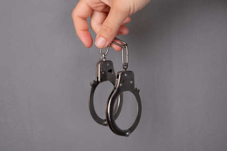 handcuffs on gray background, punishment for a crime.