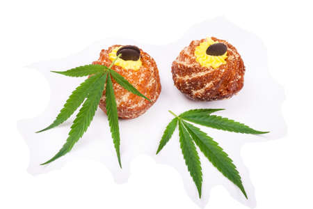 marijuana leaves and cupcakes with THC isolated on white background.