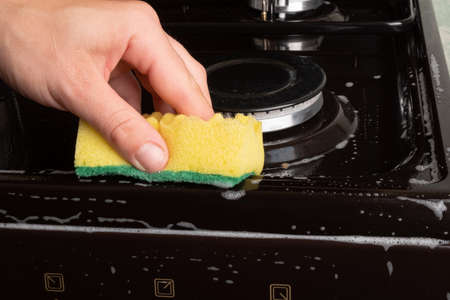 washing the gas stove in the kitchen with a washcloth . 免版税图像