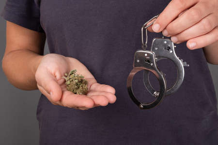 girl holding in hand a bud of marijuana and handcuffs on a dark background close-up, illegal drug.