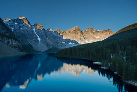 Sun rising view a top of a peak overlooking Lake Moraine in Banff National Park.