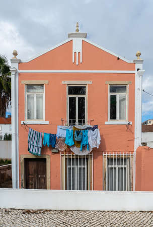 Colorful clothes hang drying outside of a house in Lisbon, Portugal.