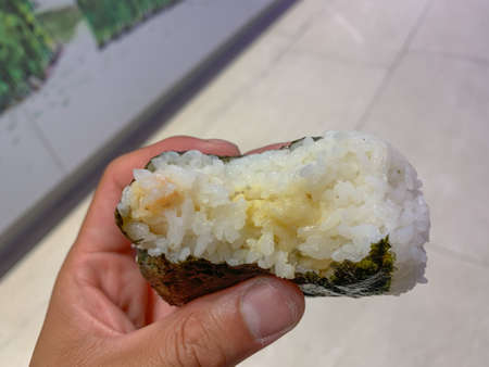 Hand holds a partially eaten Tuna and Mayonnaise Onigiri. Onigiri is a popular snack in Japan. It can usually be found in the deli area of Japanese grocery or convenient stores.