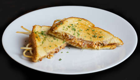 A Spaghetti Grilled Cheese Sandwich Mash Up. Homemade fusion on a white plate with black background.