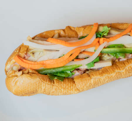 A close-up of a traditional Banh Mi Sandwich. Banh Mi Sandwiches came from the influence of the French colonization. The sandwich is typically made with a fusion of different meats and vegetables.