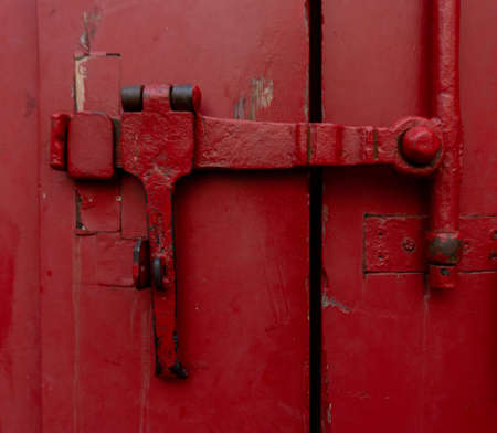 Red industrial rustic locks two large gate doors. Banco de Imagens