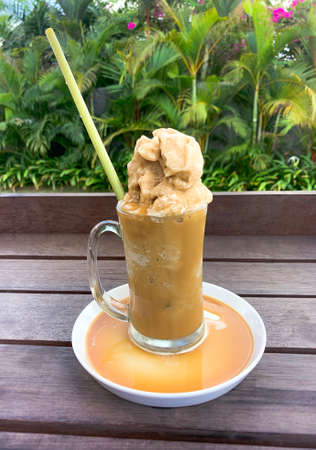 Healthy frozen iced almond milk latte with a young bamboo biodegradable straw in a tropical outdoor setting with palm trees in Canggu, Bali, Indonesia.
