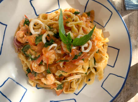 Shrimp, calamari, herbs, handmade  Italian pasta linguine entree. Natural daylight tree shadow dapple close-up on table. Reklamní fotografie