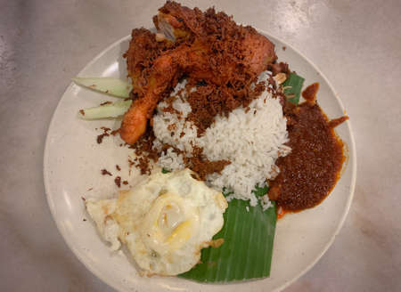 Nasi Lemak is considered a national dish in Malaysia. A fragrant rice dish cooked in coconut milk and pandan leaf. Stock Photo