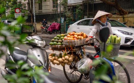 Hanoi, Vietnam - November 13,2019 : Asian woman walking bike, fruit vendor