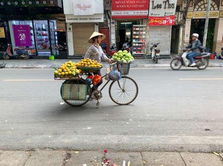 Hanoi, Vietnam - November 15,2019 : Asian woman walking bike, fruit vendor