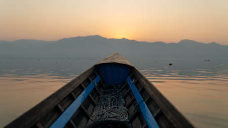 Boat tour point of view Inle Lake, Myanmar. Sunrise early morning mountain silhouette tranquil freshwater fishing lake. Over twenty species of snails and nine of fish found nowhere else in the world. Foto de archivo