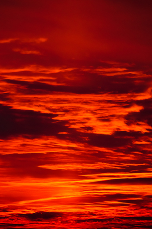 Burning evening sky at sunset. The sun is leaving the last sunbeams behind which color the heaven in dynamic illumination. Stock Photo