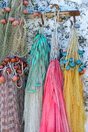 Fishing nets and ropes neatly arranged hanging on a wall to dry. Stock Photo