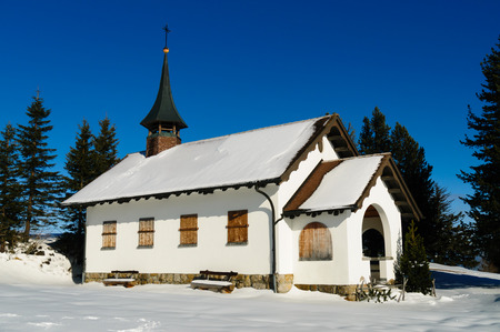A nice wintery scene in the alps with a rural church located on top of a hill.
