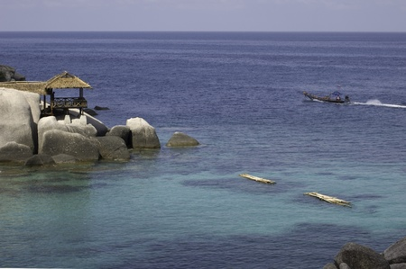View of shores of Koh Tao island : rocks, wood bungalow, crystal water, and long-tail boat. photo