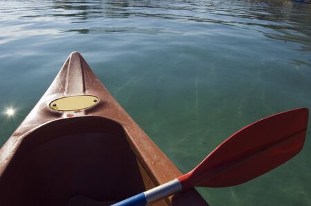 nautic: The front of a red canoe and paddle on a lake
