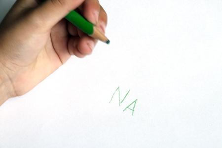 na: Child hand just writing the word NA for na-na-na-na or na na nere, expression of mocking someone