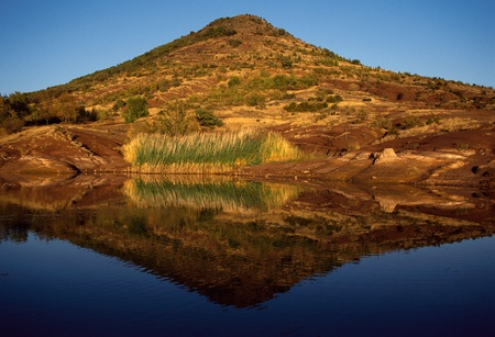 Mountain at Salagou Lake and reflection in water, by sunset light