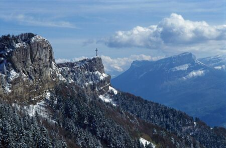 Snowed cross of Nivolet int Bauges and mountain of the Granier near Chambery, France photo