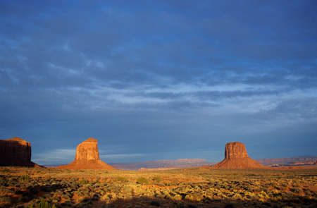 Two monts of Monument valley at sunset by a stormy day with a large amount of sky