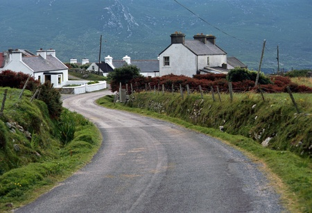 achill: Whites houses with lime and road from Doogort village in Achill island by a rainy day- Ireland