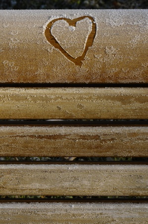 missive: Heart drawn in the frost on a wooden bench Stock Photo