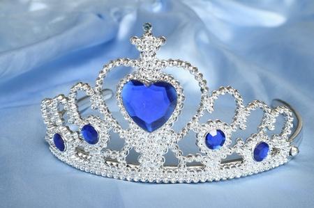 saffier: Toy tiara met diamanten en blauwe edelsteen, als een prinses kroon, op blauw satijn weefsel Stockfoto