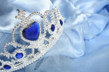 cinderella: Toy tiara with diamonds and blue gem, like a princess crown, on blue satin princess robe