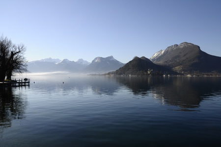 Annecy lake and mountains, view from Talloires, on morning with some mist and reflections in water photo
