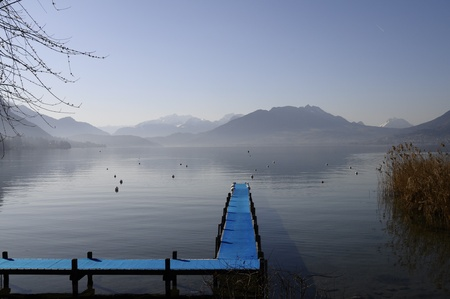Blue pontoon and view of annecy lake and mountains on winter morning photo