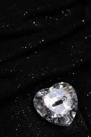 fake diamond: Heart shaped fake diamond on black background tissue with brilliant spots Stock Photo