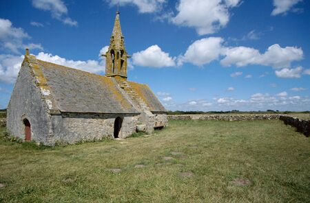 Stone church of Saint Vio  St-Vio  with orange lichens and blue sky with clouds in Brittany, France photo